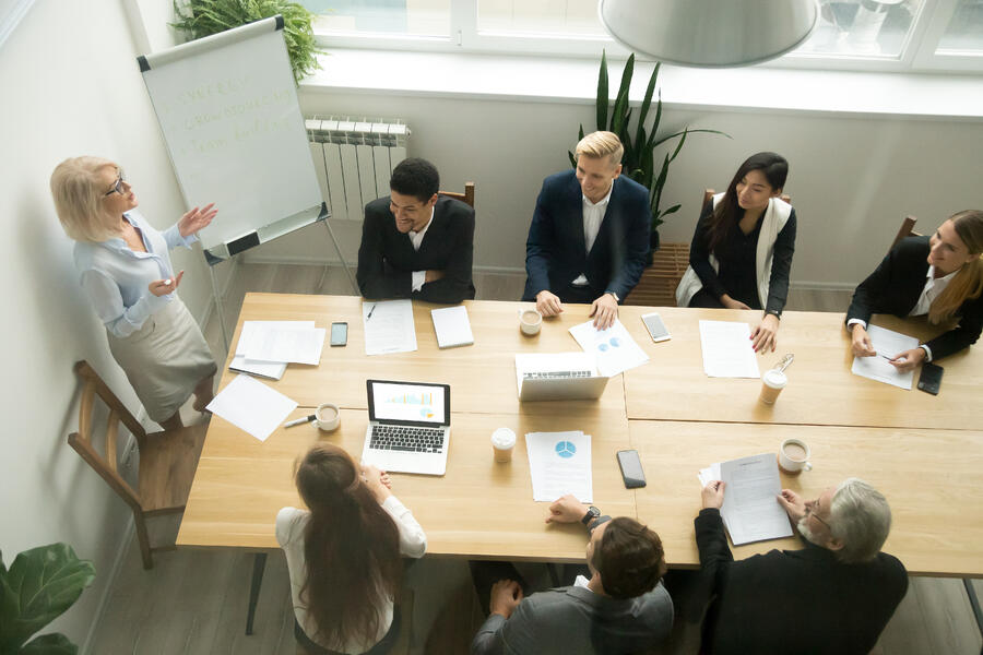 aged-senior-businesswoman-giving-presentation-multiracial-group-office-meeting